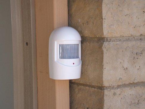 Driveway alert sensor installed at side of garage door, looking along driveway