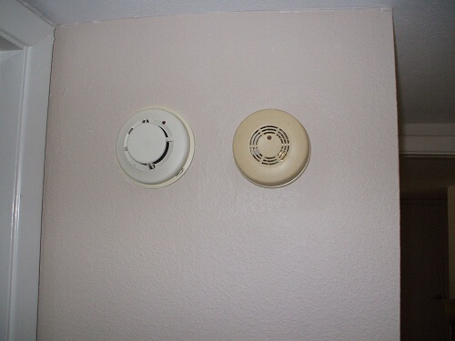 Electric smoke detector beside photoelectric smoke alarm