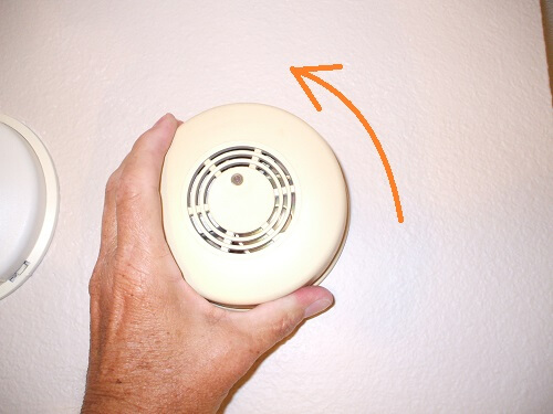 Remove old electric smoke alarm by rotating counterclockwise