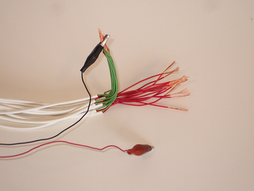 Continuity beeper connected to all green wires twisted together, ready to swipe across red wires to find the short